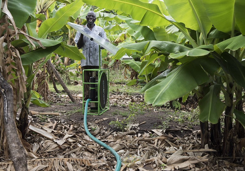 Joseph, a farmer in Kendu Bay, Kenya, smiles with his Sunflower solar irrigation system that helps keep his banana crops healthy and growing year round.